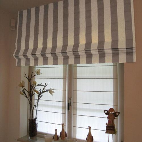 Faltrollo mit Blockstreifen grau weiß vor Biesenfaltrollos auf Fensterrahmen